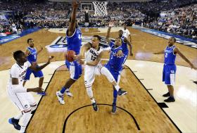Connecticut guard Shabazz Napier (13) passes around Kentucky center Dakari Johnson (44) to center Amida Brimah (35) as guard James Young (1) helps during the first half of the NCAA championship game.