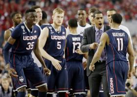 Connecticut head coach Kevin Ollie, Amida Brimah (35), Niels Giffey (5) and Ryan Boatright (11) cheer at a break against Florida during the first half of the NCAA Final Four tournament college basketball semifinal game Saturday, April 5, 2014, in Arlington, Texas.