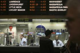 Long Island Rail Road employees work at the ticket counter in Penn Station.