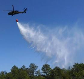 A blackhawk helicopter dropping water over the Pine Barrens in a training exercise