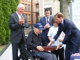US Senator Richard Blumenthal presents an American flag to William Finch Snr. at a ceremony. His son Bridgeport Mayor Bill Finch (on left), his grandson and his great grandson look on.