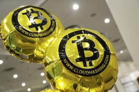 Balloons bearing the bitcoin logo float above the floor at the Inside Bitcoins conference and trade show, Monday, April 7, 2014 in New York.