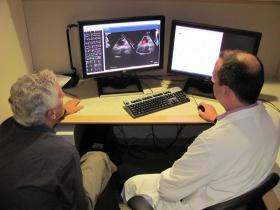 Doctor John Fahey (left) and Doctor Robert Elder (right) reviewing a Congenital Heart Defect patient's ultrasound echo.