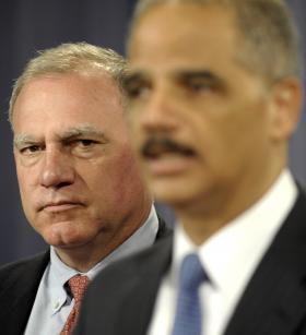 Connecticut Attorney General George Jepsen listens at left, as Attorney General Eric Holder speaks during a news conference at the Justice Department in Washington, Wednesday, April 11, 2011.