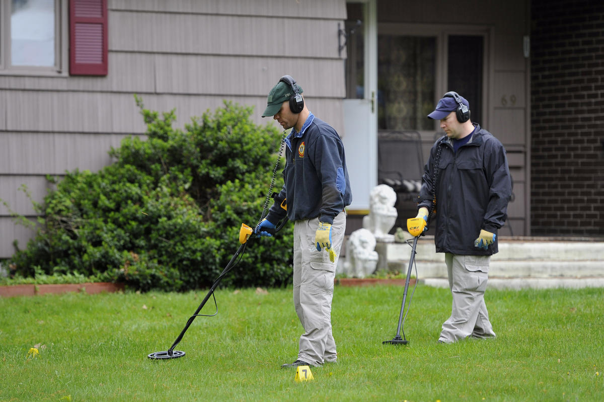 Law enforcement agents search the yard at the home of reputed Connecticut mobster Robert Gentile in Manchester, Connecticut, Thursday, May 10, 2012.