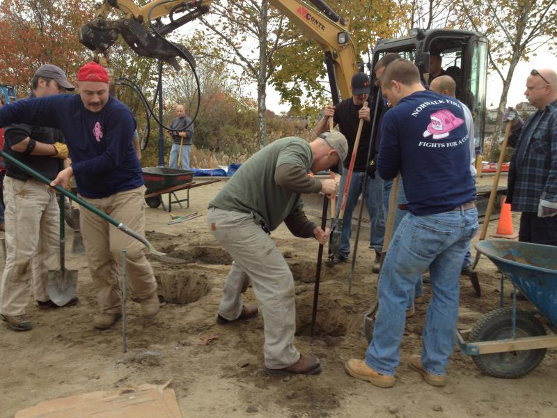 Volunteers dig holes for the supports for the new playground in honor of Allison Wyatt