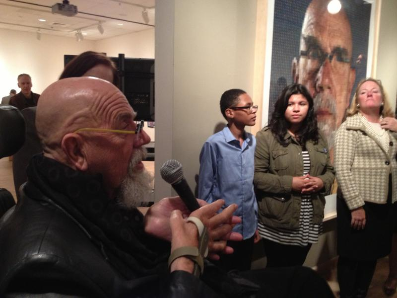 Chuck Close speaks to the crowd in Bridgeport Thursday evening, as students Chunjang Bruynder (left) and Stella Alexander listen, standing in front of a Close self portrait