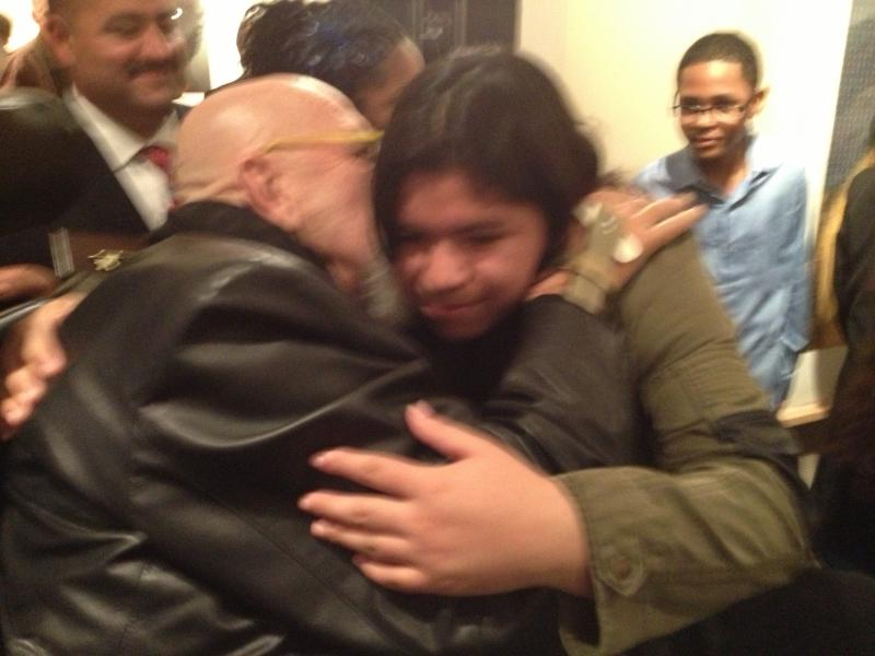 Artist Chuck Close hugs Bridgeport student Stella Alexander