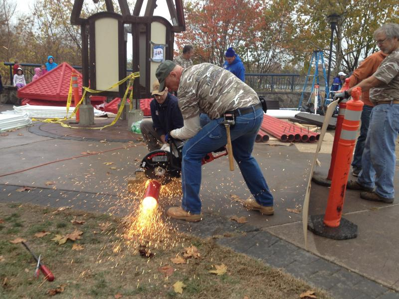 A volunteer cuts a metal pipe that will be part of the new playground