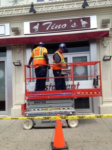 Workers prepare to dismantle the Tino's sign from the building at 84 West Park Place in Stamford, Conn.