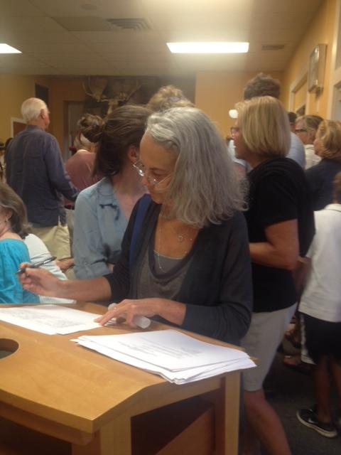 Rowaton resident Drew Lamm signs in at the meeting of the Sixth Taxing District on July 9, 2014.