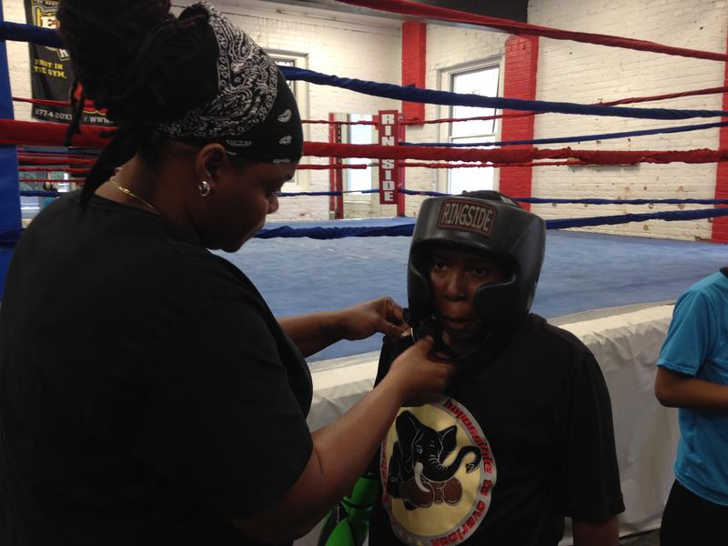 Devonne Canady helps a young boxer with his padded boxing helmet