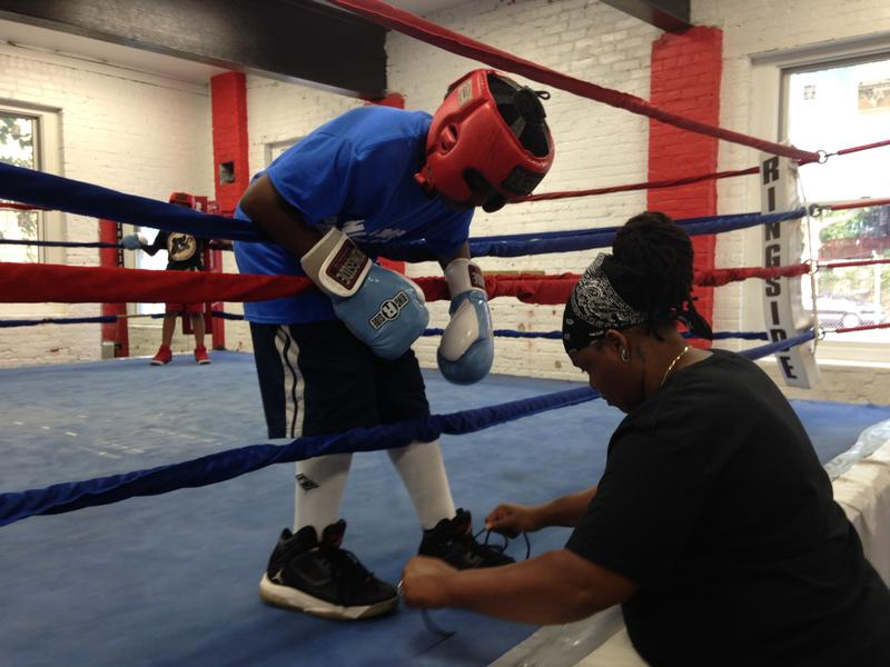 Devonne Canady ties the shoes of a boxer