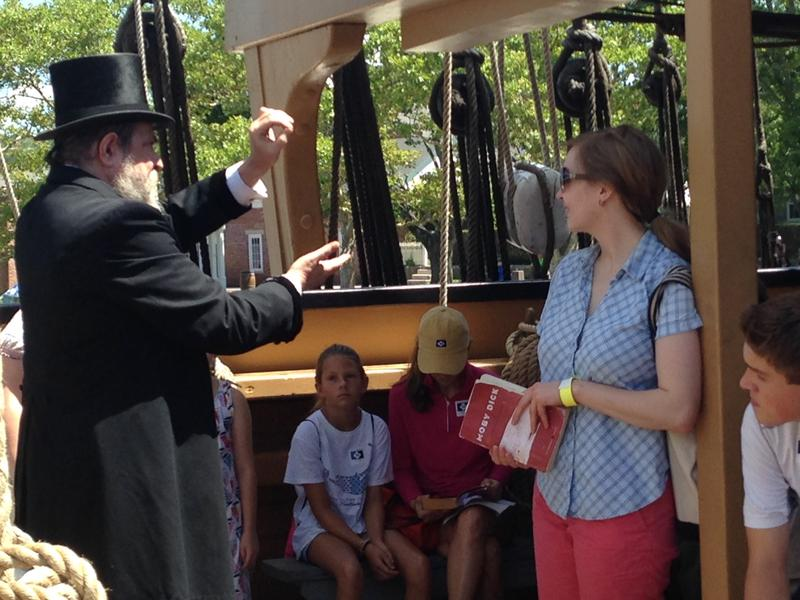 Visitors gathered on the deck of the Charles W. Morgan listen to Bill Steinmeyer portray Herman Melville.