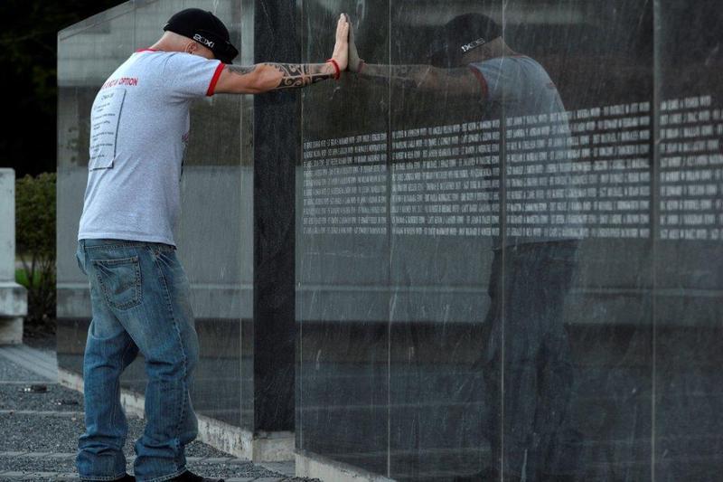 John Feal leans on the memorial at 9/11 Responders Remembered Memorial Park in Nesconset, N.Y.