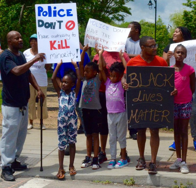 Demonstrators for the Black Lives Matter movement holding signs on the sidewalk in Riverhead, N.Y., on Sunday.