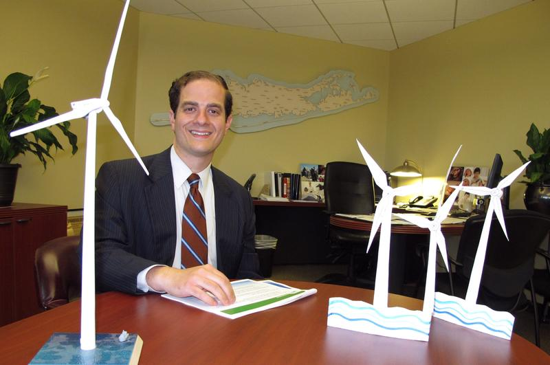 Long Island Power Authority Chief Executive Officer Thomas Falcone sits in front of some models of offshore wind turbines at the utility's offices in Uniondale, N.Y. in July. LIPA hopes to construct the nation's largest wind energy farm off Long Island.