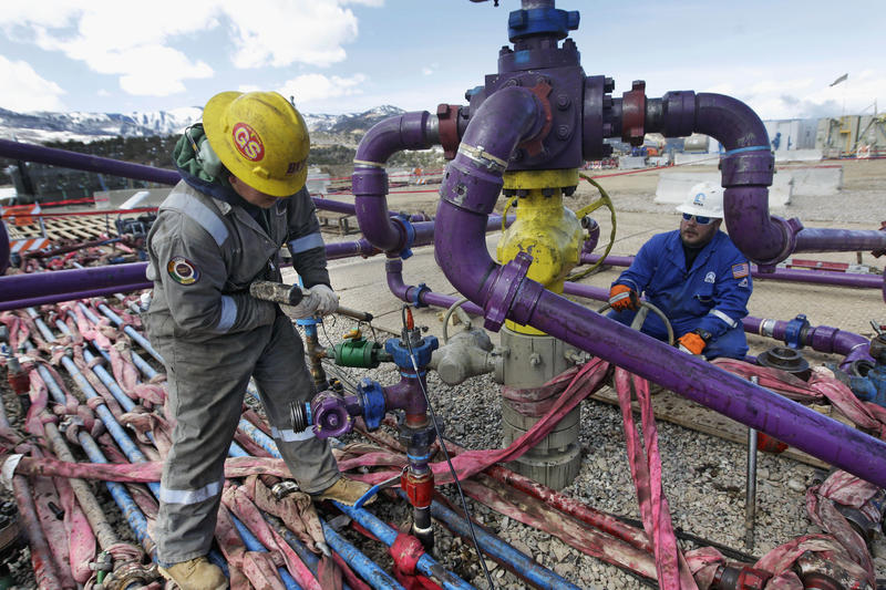 Workers tend to a well head during a hydraulic fracturing operation outside Rifle, Colo., in 2013.
