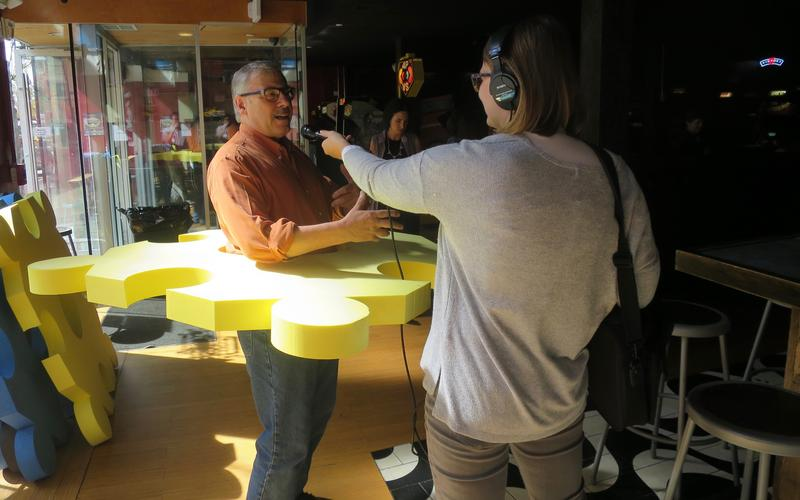 """Artist Bob Gregson being interviewed by WSHU's Cassandra Basler, while demonstrating his """"People Puzzle,"""" one of City-Wide Open Studios' """"GAME ON!"""" art installations in New Haven this fall."""