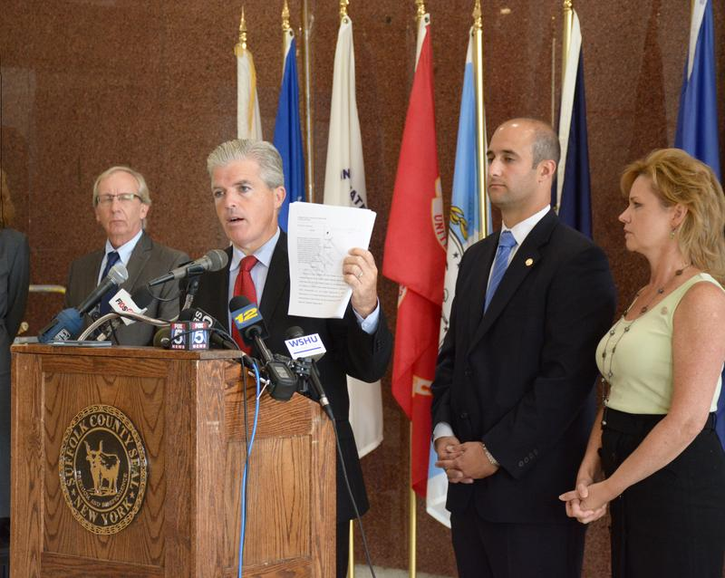 Suffolk County Executive Steve Bellone holds a copy of the lawsuit during a press conference on Wednesday. Standing behind him are Dennis Brown, county attorney; Legislator Robert Calarco; and Legislator Sarah Anker.