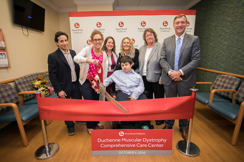 Javier Romero, seated, Duchenne muscular dystrophy patient and namesake of Hope For Javier, is surrounded by family and Stony Brook physicians at the ribbon cutting for the Duchenne Muscular Dystrophy Comprehensive Care Center.