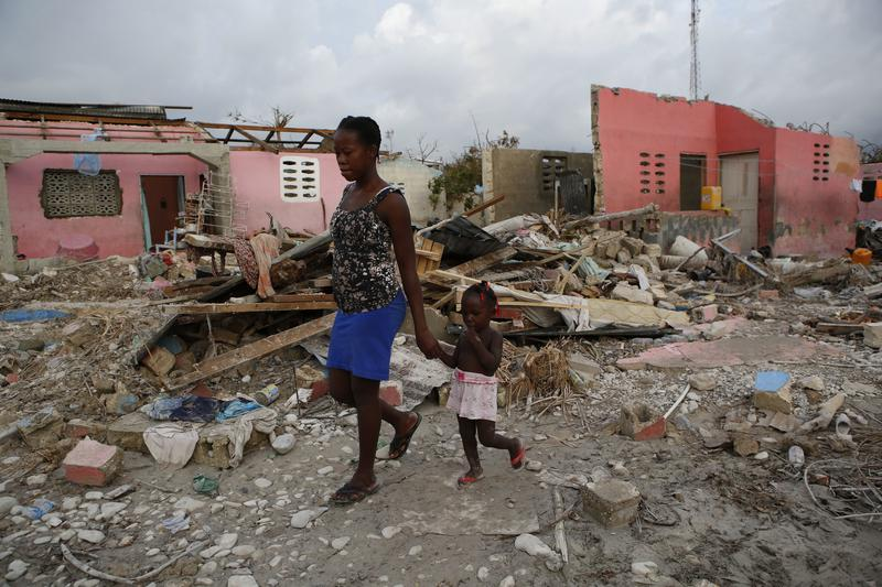 Residents walk amidst damaged buildings and debris in a seaside fishing neighborhood almost completely destroyed by Hurricane Matthew, in Port Salut, Haiti, on Sunday.