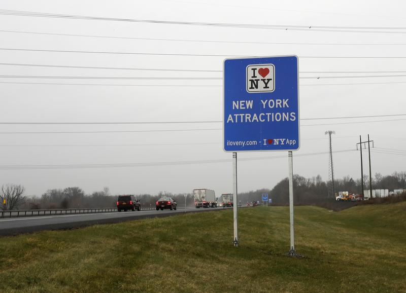 "Vehicles pass an ""I Love New York"" sign on the New York State Thruway in Utica, N.Y., in 2016. FHA officials say the signs don't conform to federal standards and pose a dangerous distraction for motorists."