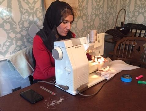 Manal, a widowed refugee from Syria, with the sewing machine she has on loan. She hopes to earn money for herself and her five children by making pillows and curtains.