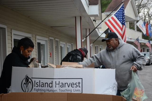 A volunteer from Island Harvest assists a veteran at the distribution site on Thursday.