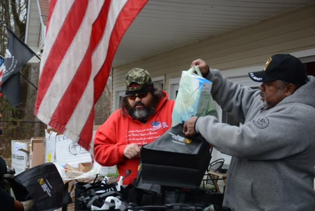 A veteran helps his fellow veteran pack a turkey and other food for holiday dinner.
