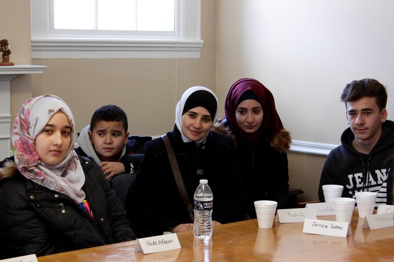 Two of Farida Al-Faouri's four children, left, sit beside other newly arrived refugees from Syria at Friday's welcome gathering for the Al-Faouri family at the International Institute of Connecticut's headquarters in Bridgeport, Conn.