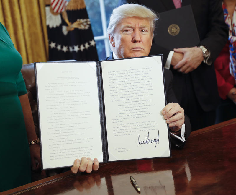 President Donald Trump holds up an executive order after signing it in the Oval Office of the White House in Washington in February. The executive order directs the Treasury secretary to review the 2010 Dodd-Frank financial oversight law.