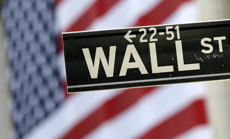 A Wall Street street sign is framed by an American flag hanging on the facade of the New York Stock Exchange in 2015.