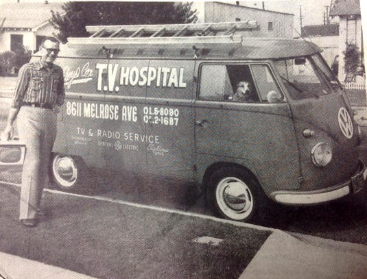 TV and radio repairman Floyd Cox in front of his VW service van, pictured with his canine assistant in the passenger seat.