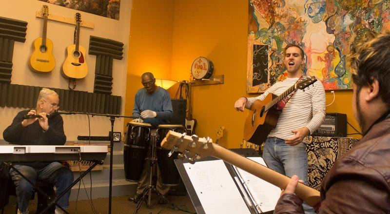 Adam Christoferson, second from right, founded Musical Intervention a year ago in New Haven. Here Christoferson leads a rehearsal before an open mic night in December.
