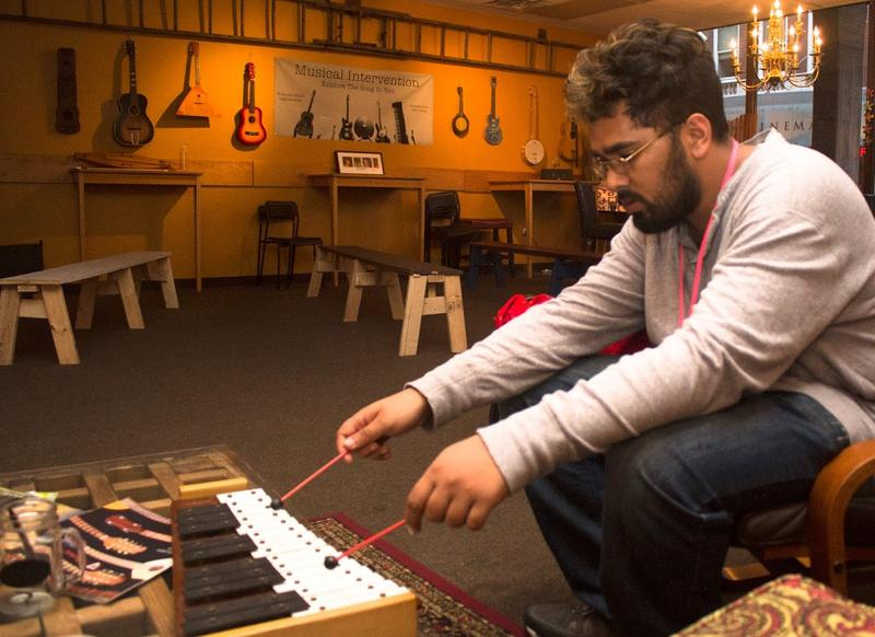A man plays a xylophone during a quieter time at the storefront.