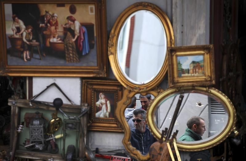Shoppers are reflected in mirrors for sale outside an antique shop in central Athens.