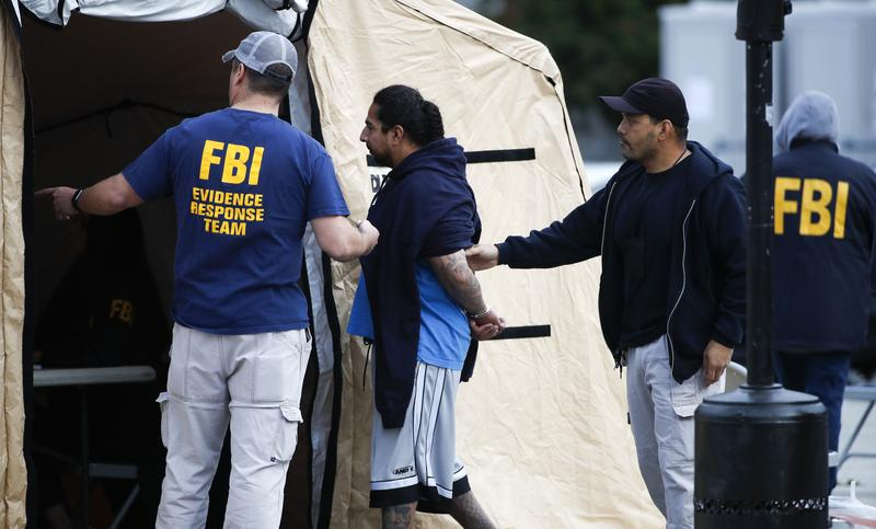 A man is taken into custody by FBI agents in May as part of a three-year investigation into the violent MS-13 gang in Los Angeles.