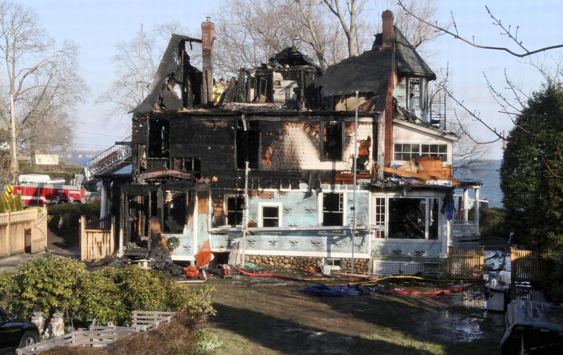 Firefighters investigate a house in Stamford, Conn., where an early morning fire left five people dead on Christmas morning 2011.