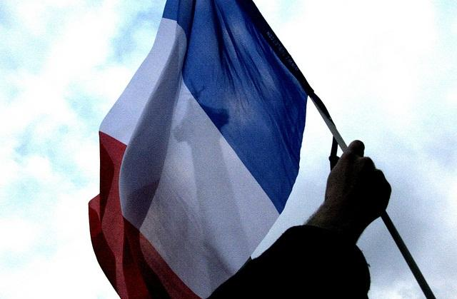 A French flag passes the column of Place de la Bastille in May 2012.