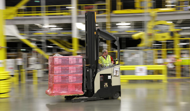 A worker places an item in a box for shipment at a Amazon.com fulfillment center in DuPont, Wash.