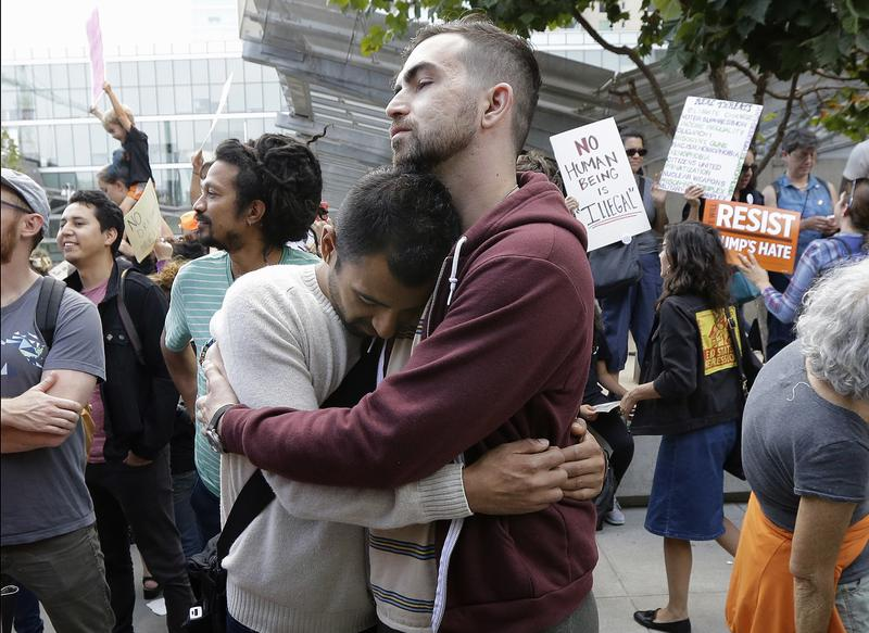 Deferred Action for Childhood Arrivals (DACA) recipient Alejandro Lopez, left, hugs Steven Broderick during a protest outside of the Federal Building in San Francisco on Tuesday.