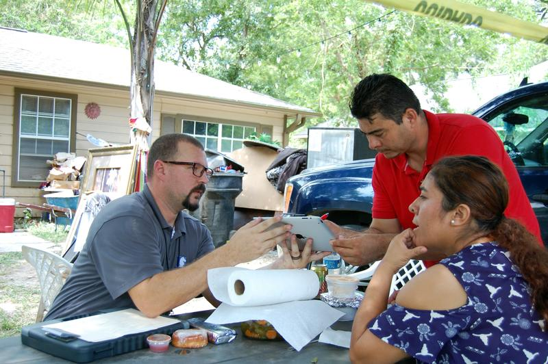 Flood adjuster James Garden has policyholders, Servando and Maria Jimas, sign paperwork detailing their flood loss after Hurricane Harvey caused catastrophic flooding in Texas.