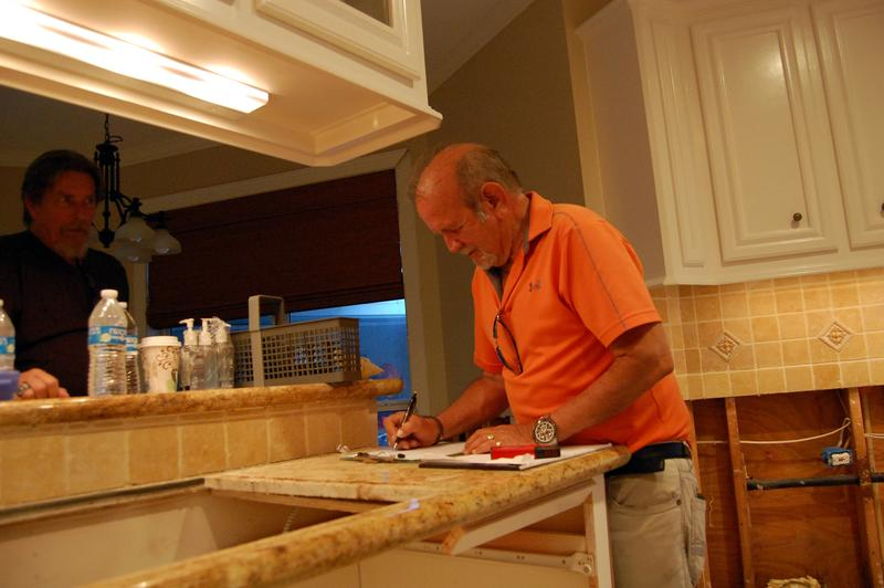 Flood adjuster Sean Westerling measures and sketches details to another flooded house in Houston.