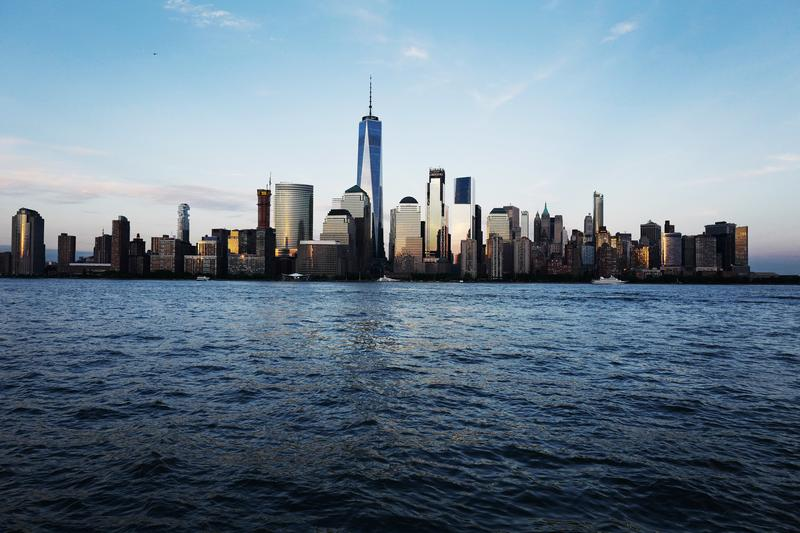 One World Trade Center towers above neighboring buildings in the New York skyline and the Hudson River.