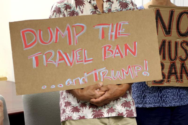 Critics of President Donald Trump's travel ban hold signs during a news conference with Hawaii Attorney General Douglas Chin in Honolulu in June.