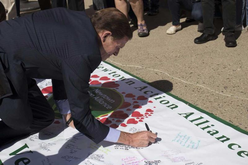Senator Blumenthal signing onto a Newtown Action Alliance banner. The alliance was founded after the 2012 Sandy Hook Elementary School Shooting in Newtown, Conn.