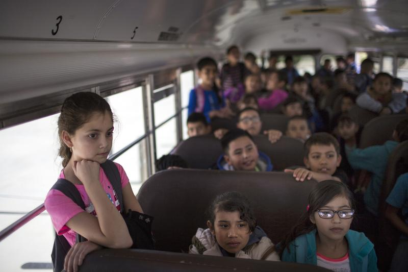 Students wait inside a school bus at Columbus Elementary School, in Columbus, New Mexico, in March.