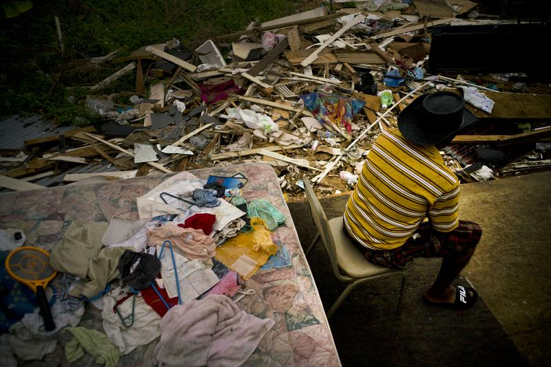 Efrain Diaz Figueroa spends the afternoon sitting on a chair next to the remains of the house of his sister destroyed by Hurricane Maria in San Juan, Puerto Rico, on Monday.