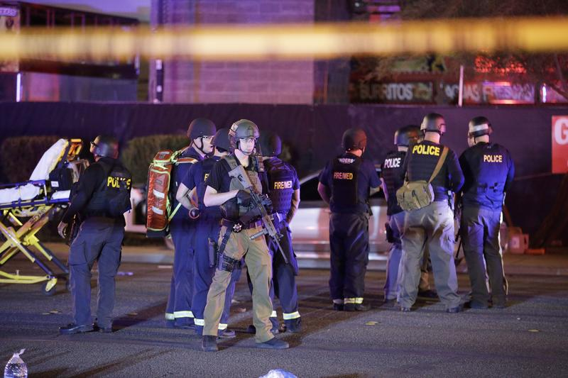 Police officers and medical personnel stand at the scene of a shooting near the Mandalay Bay resort and casino on the Las Vegas Strip on Monday.